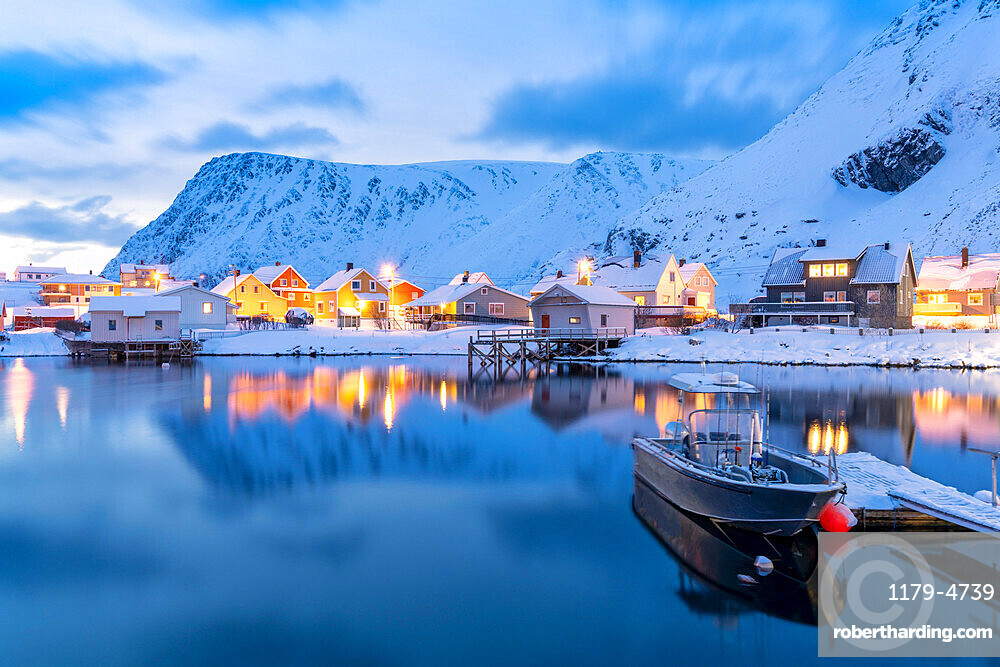 Illuminated village of Sorvaer mirrored in the cold sea during winter dusk, Soroya Island, Troms og Finnmark, Northern Norway, Scandinavia, Europe