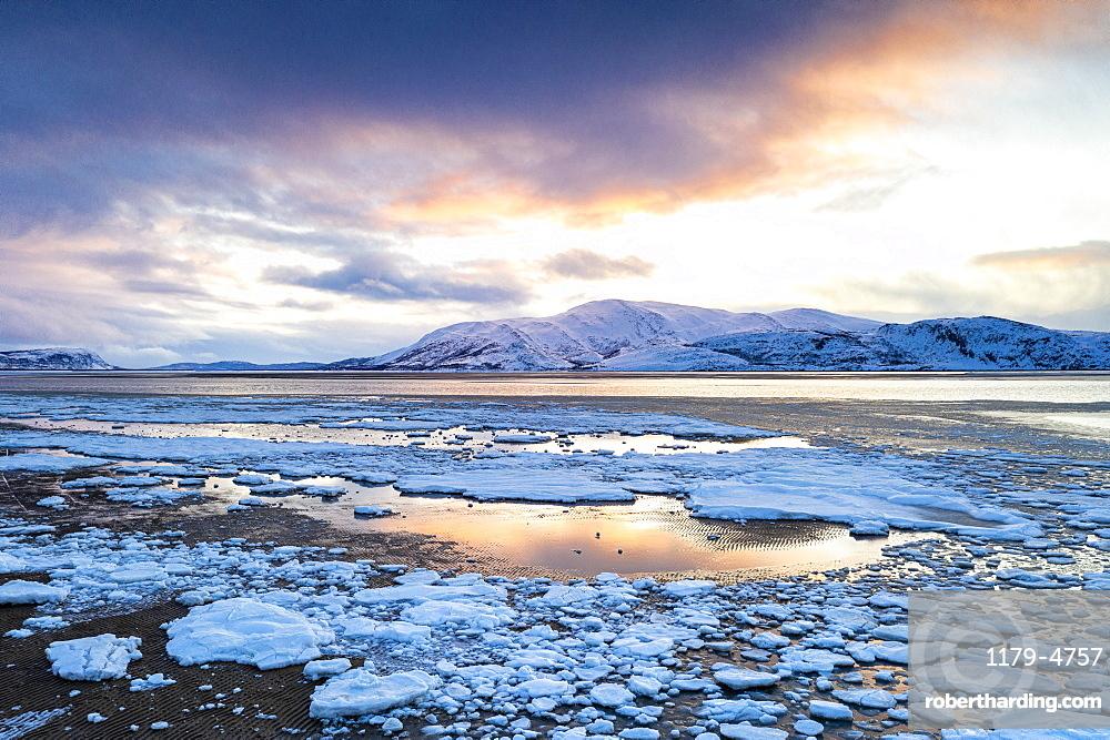 Arctic sunset on snow capped mountains and frozen sea, Tanamunningen Nature Reserve, Leirpollen, Troms og Finnmark, Arctic, Norway, Scandinavia, Europe