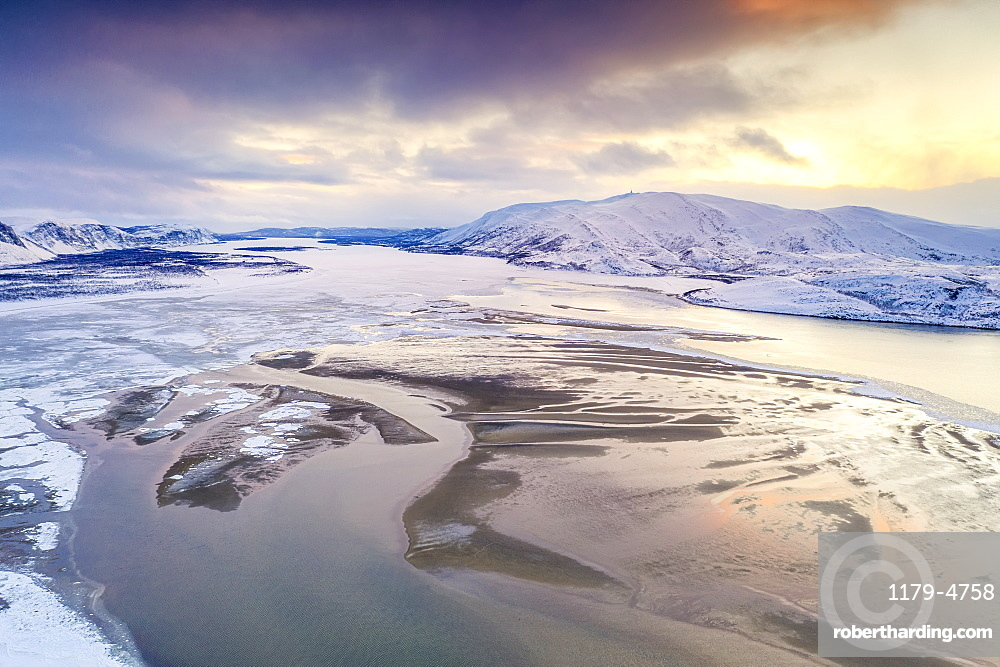 Aerial view of cold sea framed by snow capped mountains at sunset, Tanamunningen Nature Reserve, Leirpollen, Finnmark, Arctic, Norway, Scandinavia, Europe