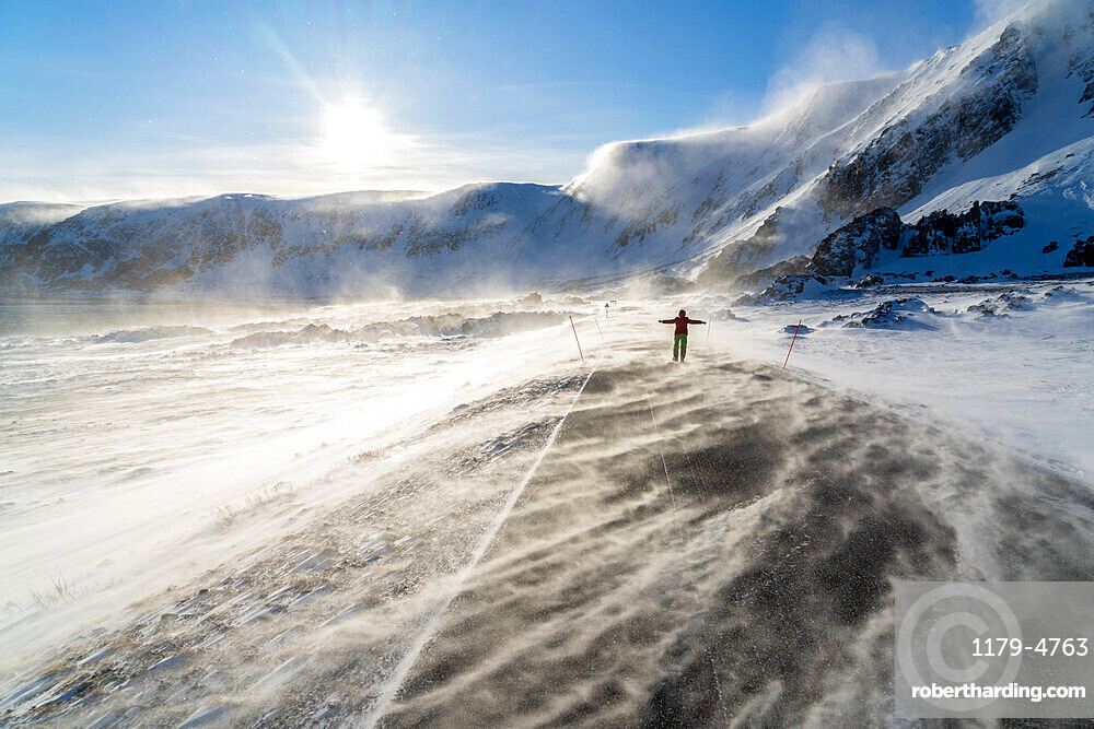 Man rejoices on icy empty road along Barents Sea during the Arctic windstorm, Berlevag, Varanger Peninsula, Finnmark, Norway, Scandinavia, Europe