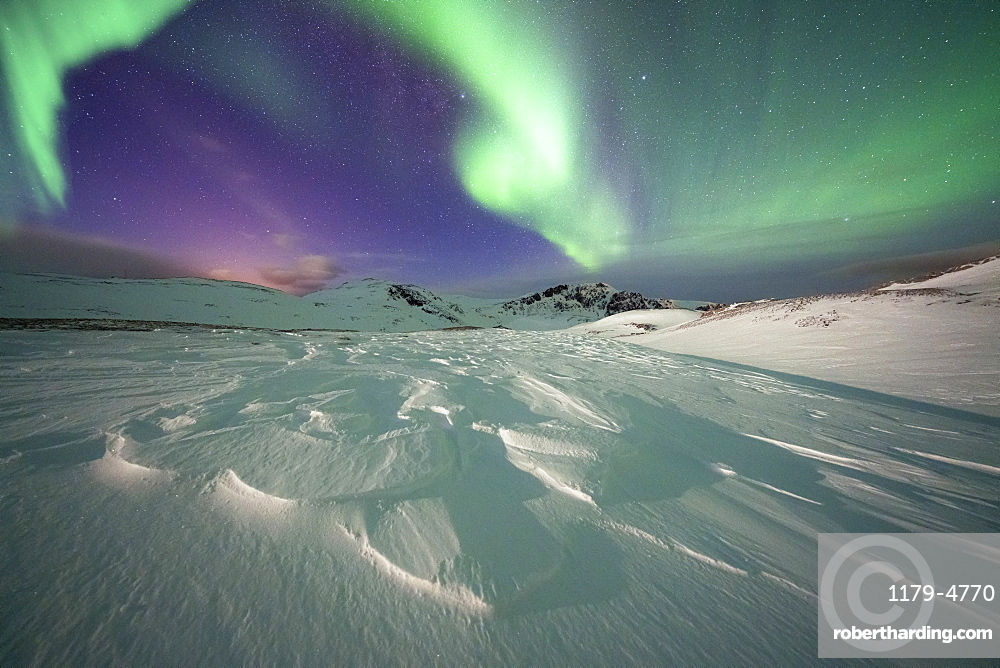 Frozen snow lit by green lights of the Northern Lights (Aurora Borealis) in the cold Arctic night, Mageroya island, Nordkapp, Troms og Finnmark, Norway, Scandinavia, Europe