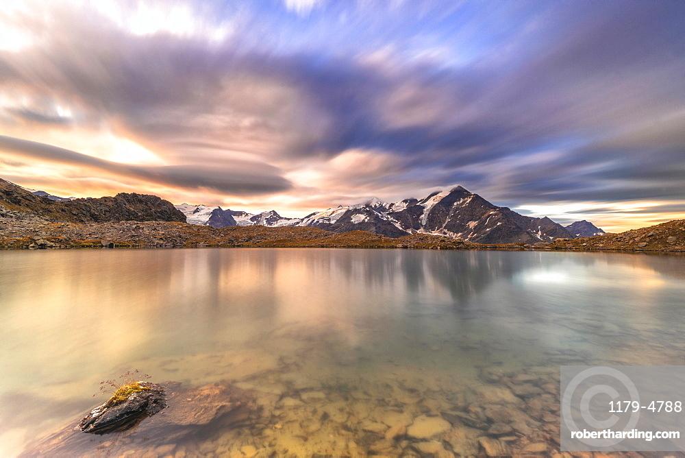 Dramatic sky at sunrise over Tresero peak reflected in lake Manzina, Valfurva, Valtellina, Sondrio province, Lombardy, Italy