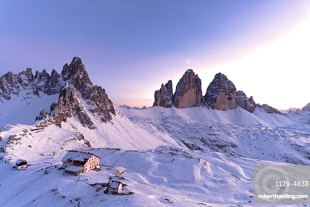 Sunset over Monte Paterno, Tre Cime di Lavaredo and Locatelli hut covered with snow, Sesto Dolomites, South Tyrol, Italy