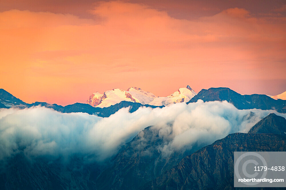 Burning sky at sunrise over the snow capped Monte Rosa surrounded by a sea of clouds, Valais canton, Switzerland