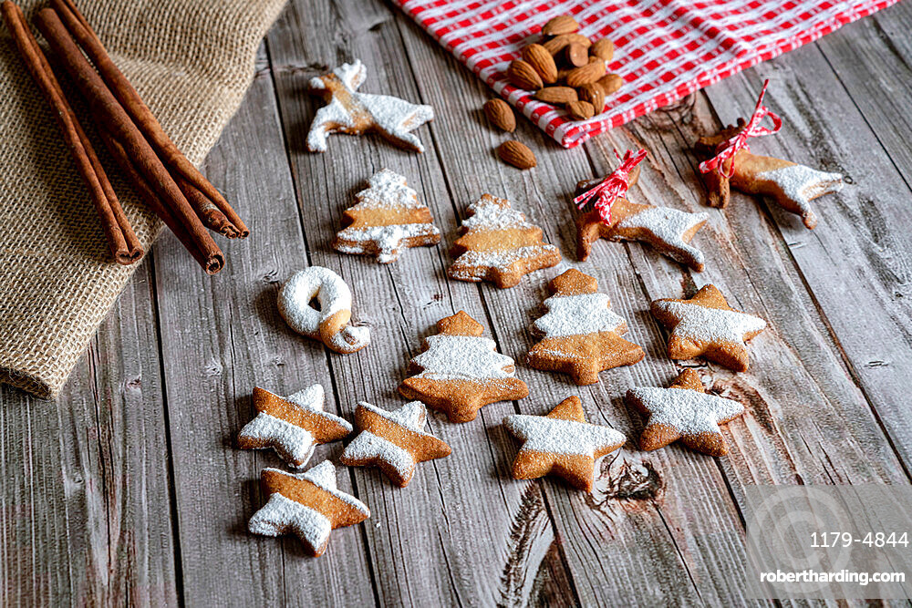 Gingerbread and butter cookies in shape of Christmas tree and stars with almond and cinnamon on wood table background