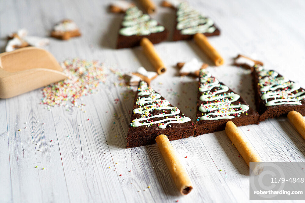 Homemade decorated chocolate brownies in shape of Christmas tree on wood table background