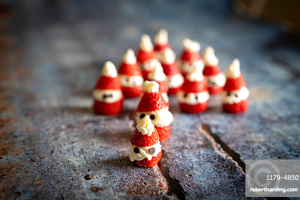 Close-up of cute strawberries shaped in Santa Claus filled with whipped cream and chocolate pieces for Christmas