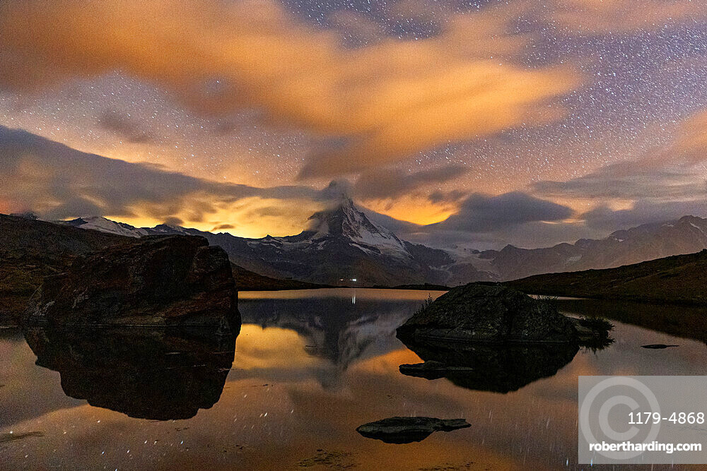 Clouds in the starry sky above Matterhorn reflected in lake Stellisee, Zermatt, Valais canton, Switzerland