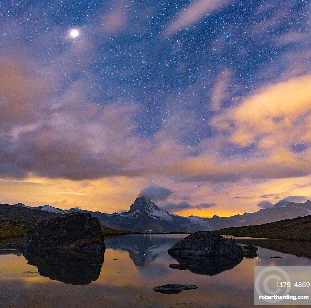 Matterhorn peak lit by moon in the starry night sky view from Stellisee, Zermatt, Valais canton, Switzerland