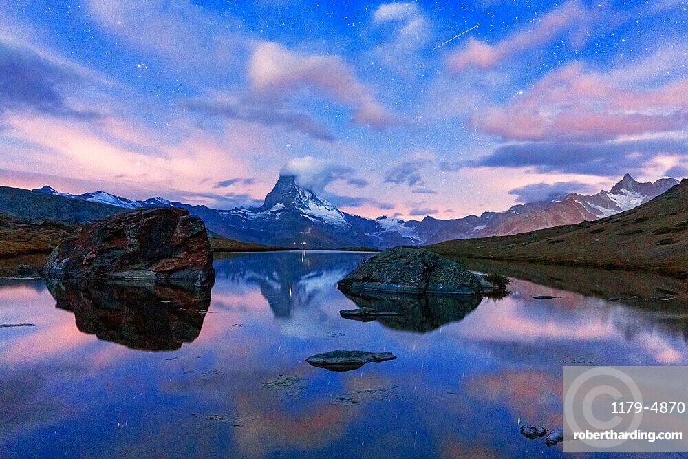 Glowing stars over Matterhorn mirrored in lake Stellisee at dusk, Zermatt, Valais canton, Switzerland