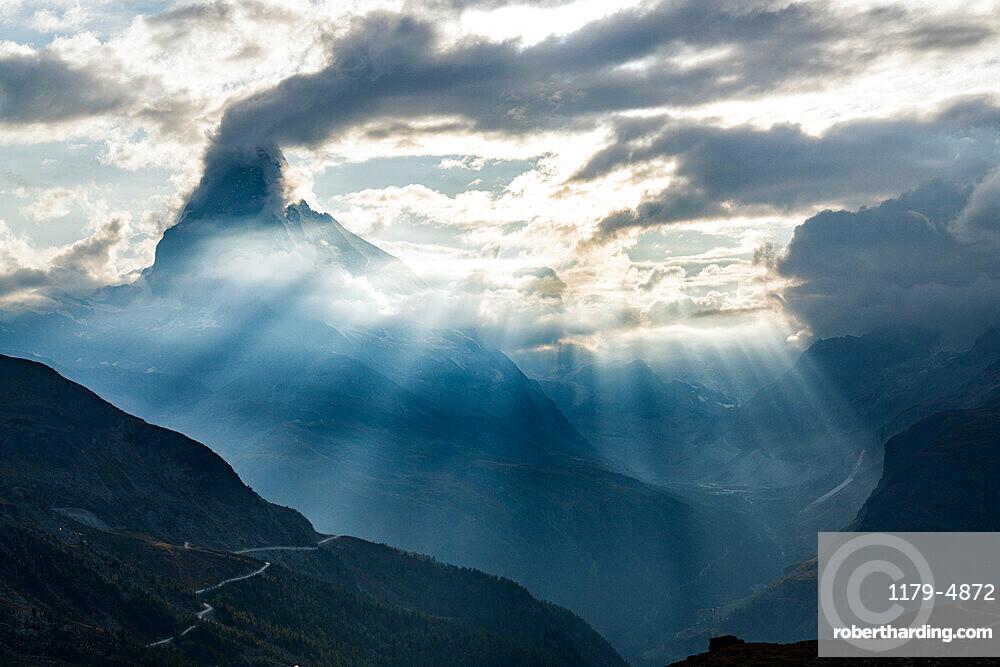 Sun rays through clouds over Matterhorn during a backlight sunset, Zermatt, Valais canton, Switzerland
