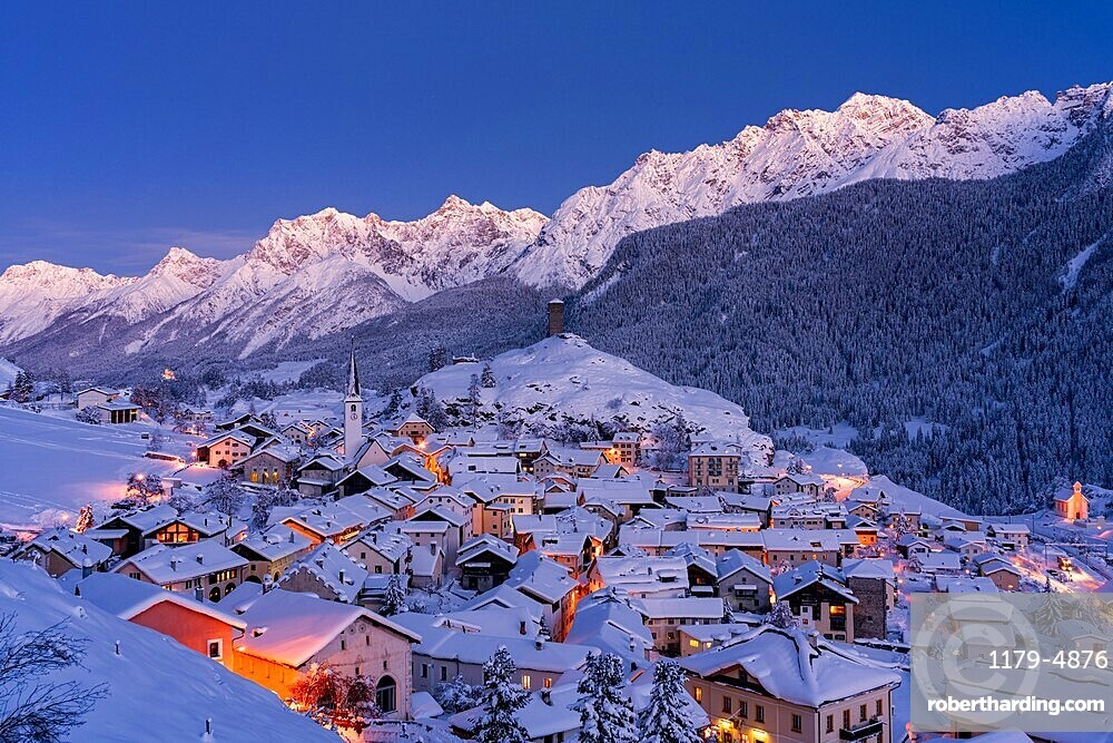Traditional houses covered with snow during the winter dusk, Ardez, canton of Graubunden, Engadine, Switzerland