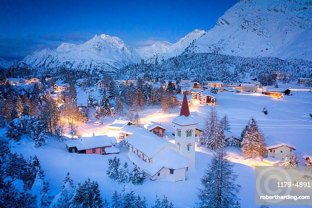 Dusk over Chiesa Bianca and Maloja village covered with snow, Bregaglia, canton of Graubunden, Engadin, Switzerland