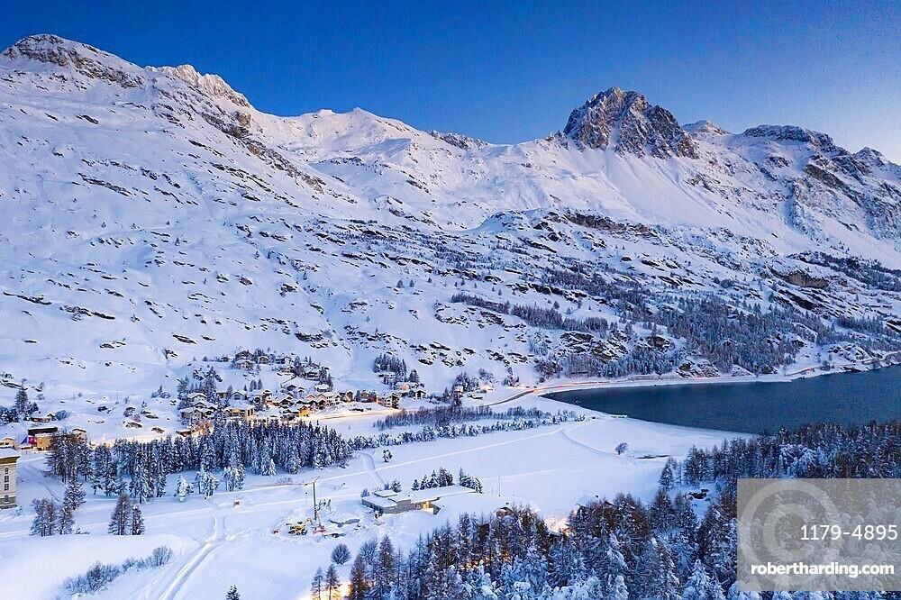 Dusk over the snow covered village of Maloja on shores of Lake Sils, Bregaglia, canton of Graubunden, Engadin, Switzerland