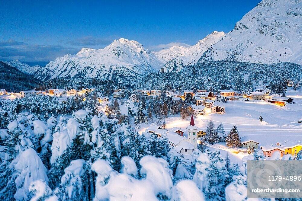 Winter forest covered with snow surrounding Chiesa Bianca and Maloja at dusk, Bregaglia, Graubunden canton, Engadin, Switzerland