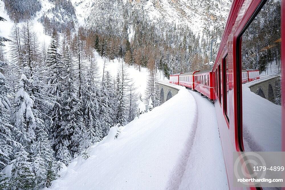 Bernina Express train in the alpine landscape covered with snow, Preda Bergun, Albula Valley, Graubunden canton, Switzerland