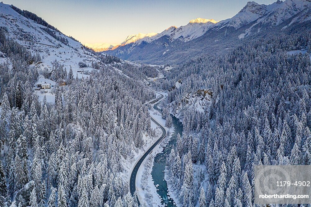 Sunrise over winding mountain road and frozen river in the forest covered with snow, Zernez, Graubunden canton, Switzerland
