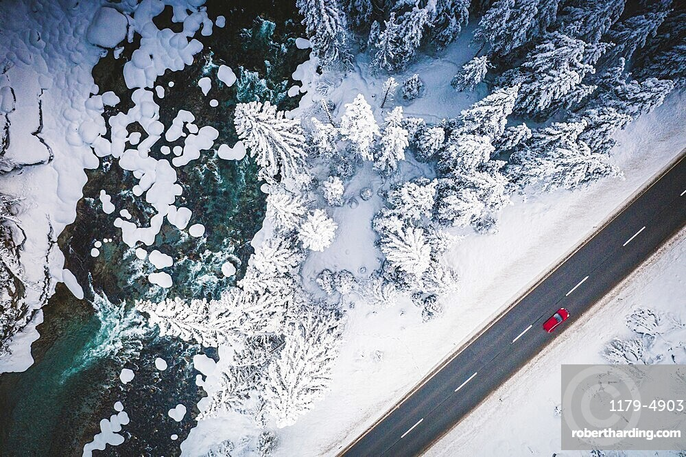 Car traveling on the snowy mountain road on side of frozen river and woods, aerial view, Switzerland