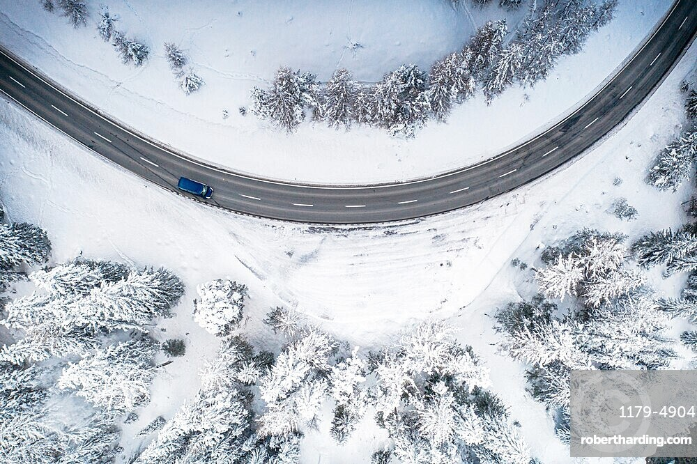 Car driving on bends on snowy mountain road from above