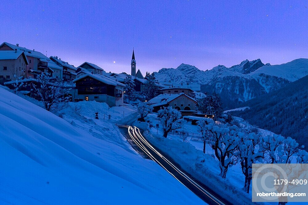Snow covered village of Guarda lit by car trail lights during a blue winter dusk, Graubunden canton, Lower Engadin, Switzerland