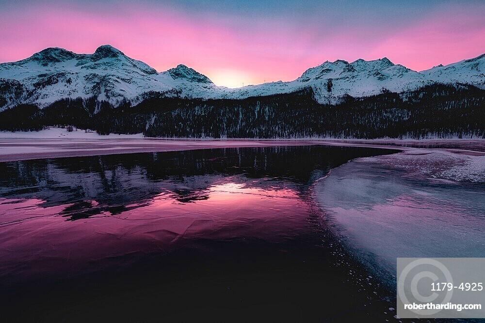 Colorful sky at sunrise on snowcapped mountains and frozen Lake Silvaplana, Maloja, Engadine, Graubunden canton, Switzerland
