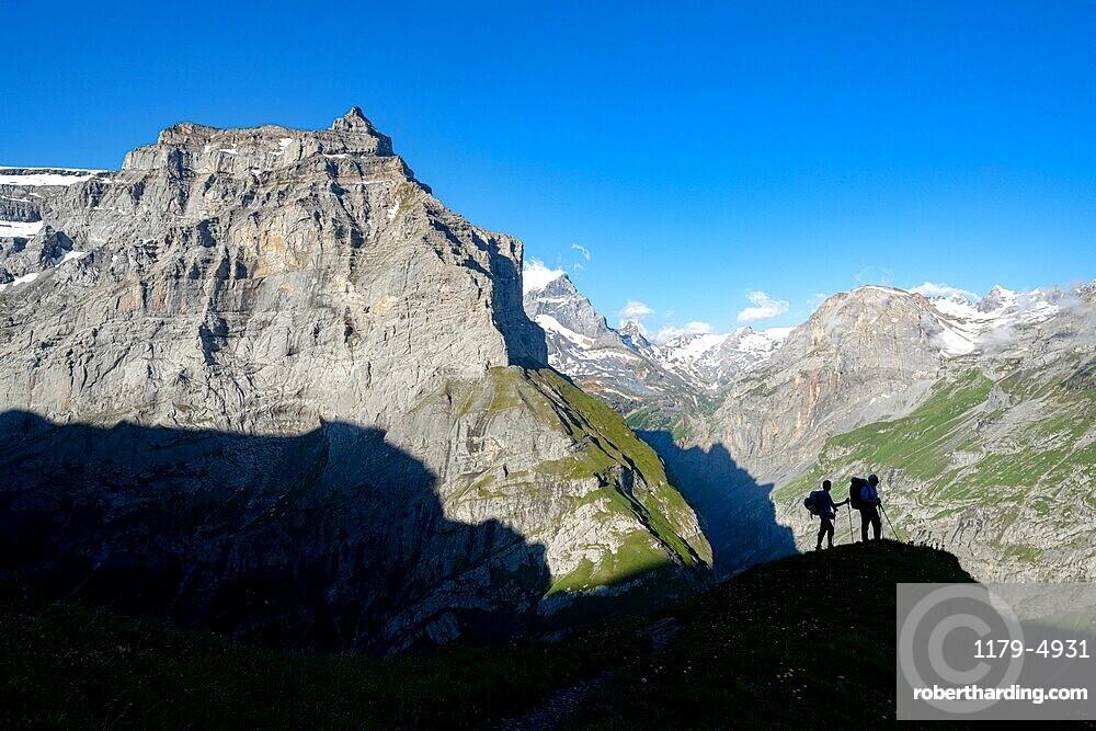 Two hikers admiring mountains during the hike towards Muttsee Hut on Kalktrittli path, Canton of Glarus, Switzerland
