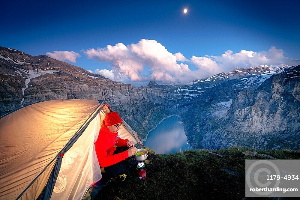 Hiker man with tent using camping stove on ridge above lake Limmernsee, Canton of Glarus, Switzerland