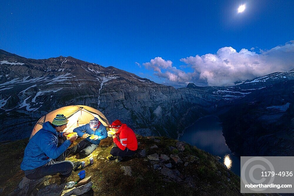 Three hikers men enjoying dinner out of a tent above lake Limmernsee at dusk, Canton of Glarus, Switzerland