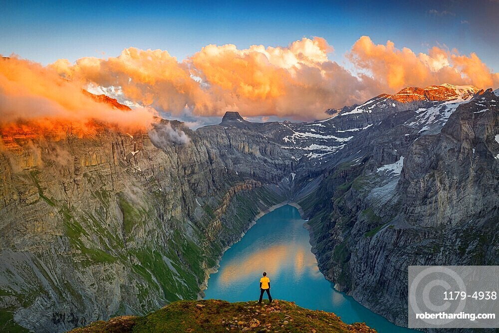 Man standing on rocks looking at clouds at sunset over lake Limmernsee, aerial view, Canton of Glarus, Switzerland
