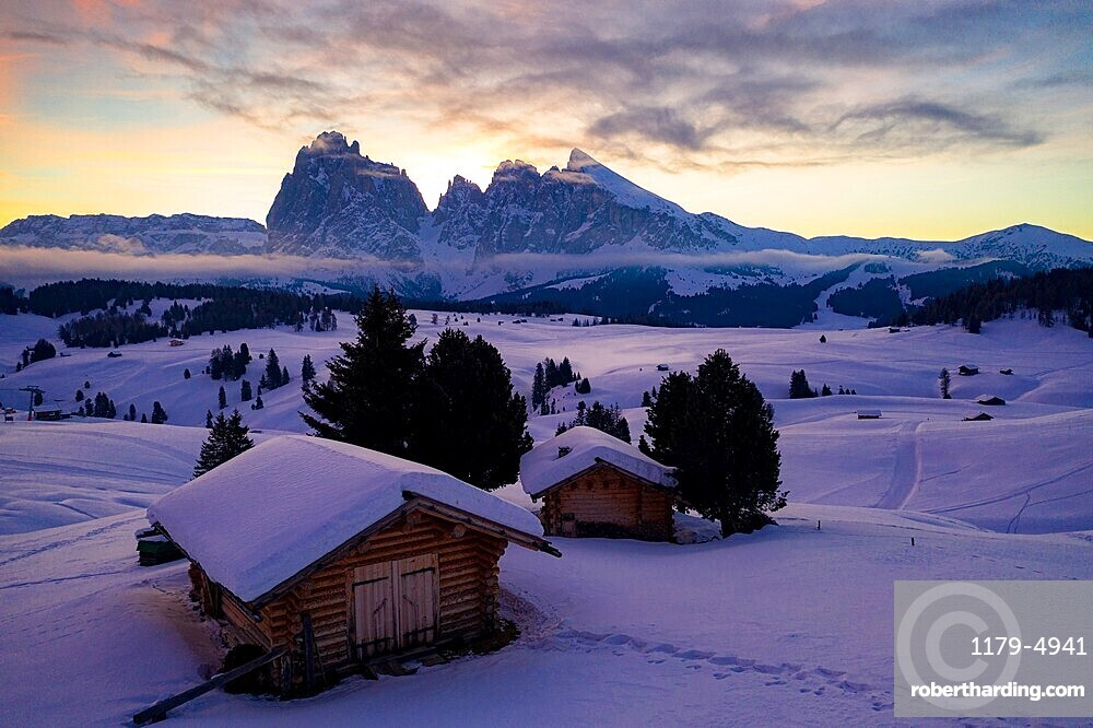 Wood cabins covered with snow with Sassopiatto and Sassolungo on background at dawn, Seiser Alm, Dolomites, South Tyrol, Italy