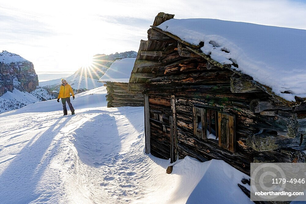Hiker man in the snowy landscape hit by the backlight sunset in winter, Passo Gardena, Dolomites, South Tyrol, Italy