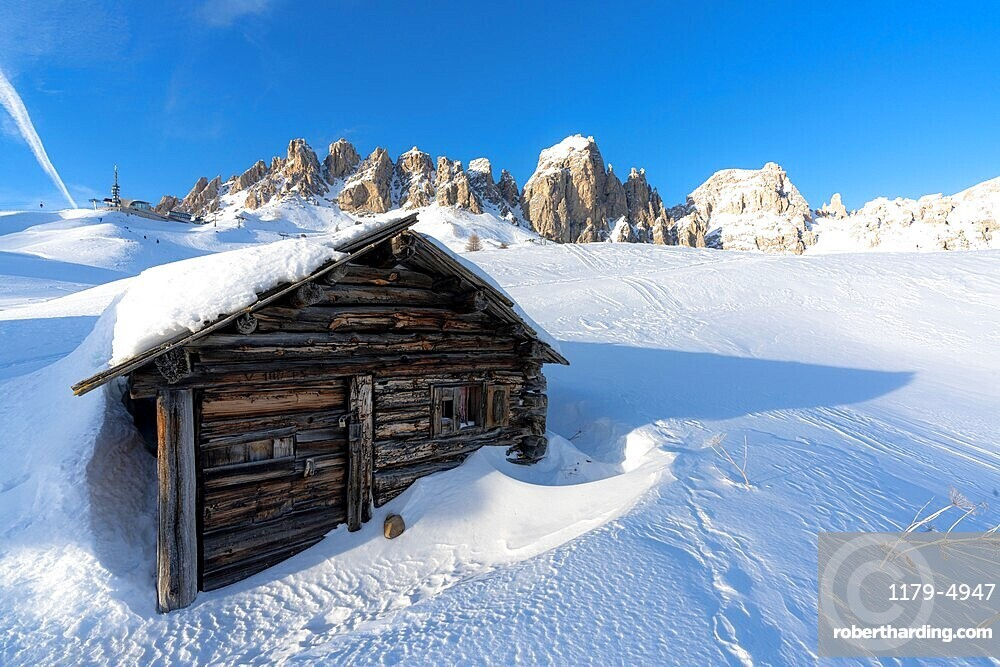 Isolated wood hut covered with snow with Cir Group peaks on background at sunset, Passo Gardena, Dolomites, South Tyrol, Italy