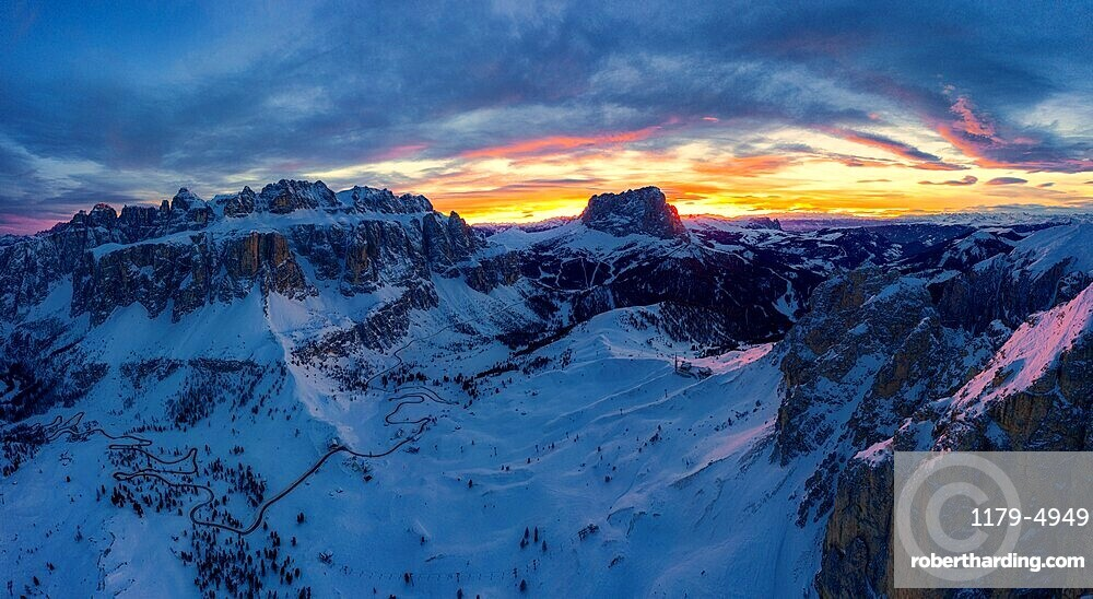 Clouds in the burning sky at sunset over Sassolungo and Sella Group mountains covered with snow, Dolomites, South Tyrol, Italy