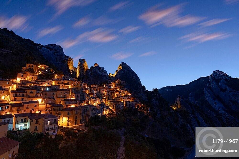 Illuminated village of Castelmezzano framed by Dolomiti Lucane peaks at sunrise, Potenza province, Basilicata, Italy