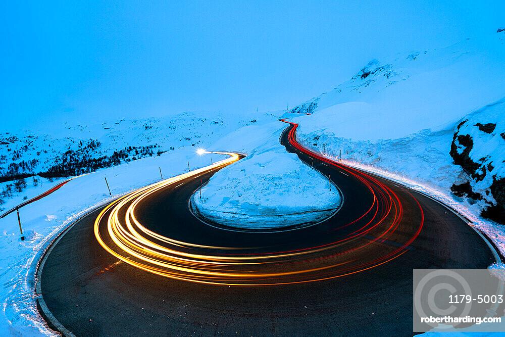 Car trail lights on bends of Bernina Pass road in winter, Val Poschiavo, canton of Graubunden, Engadin, Switzerland, Europe