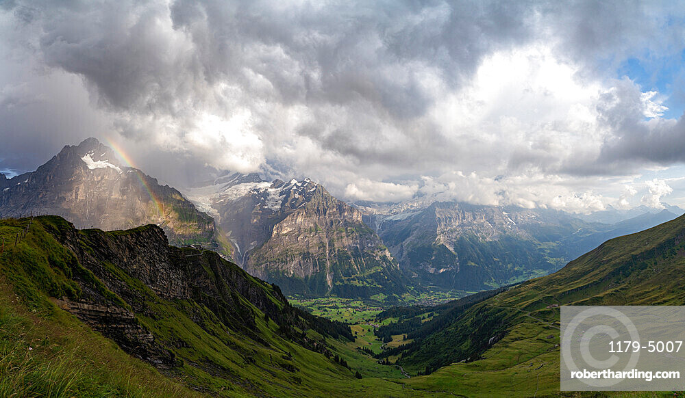 Panoramic of green valley surrounding Grindelwald and Bernese Alps lit by rainbow, First, Canton of Bern, Switzerland, Europe