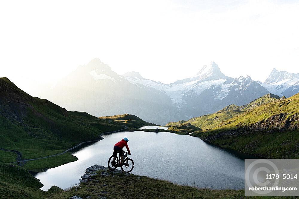 Mountain biker riding downhill at Bachalpsee lake at dawn, Grindelwald, Bernese Oberland, Bern Canton, Switzerland, Europe