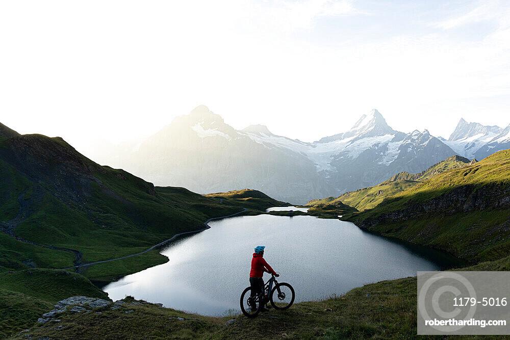 Hiker with mountain bike admiring sunrise over Bachalpsee lake, Grindelwald, Bernese Oberland, Bern Canton, Switzerland, Europe