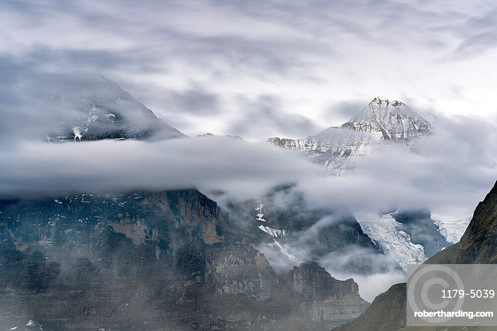 The Eiger and Monch mountain peaks in the cloudy sky, Mannlichen, Grindelwald, Bernese Oberland, Bern Canton, Switzerland, Europe