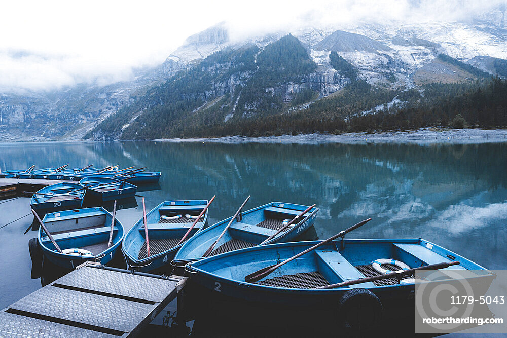 Row boats moored on shore of lake Oeschinensee on a foggy day, Bernese Oberland, Kandersteg, Bern canton, Switzerland, Eurpe