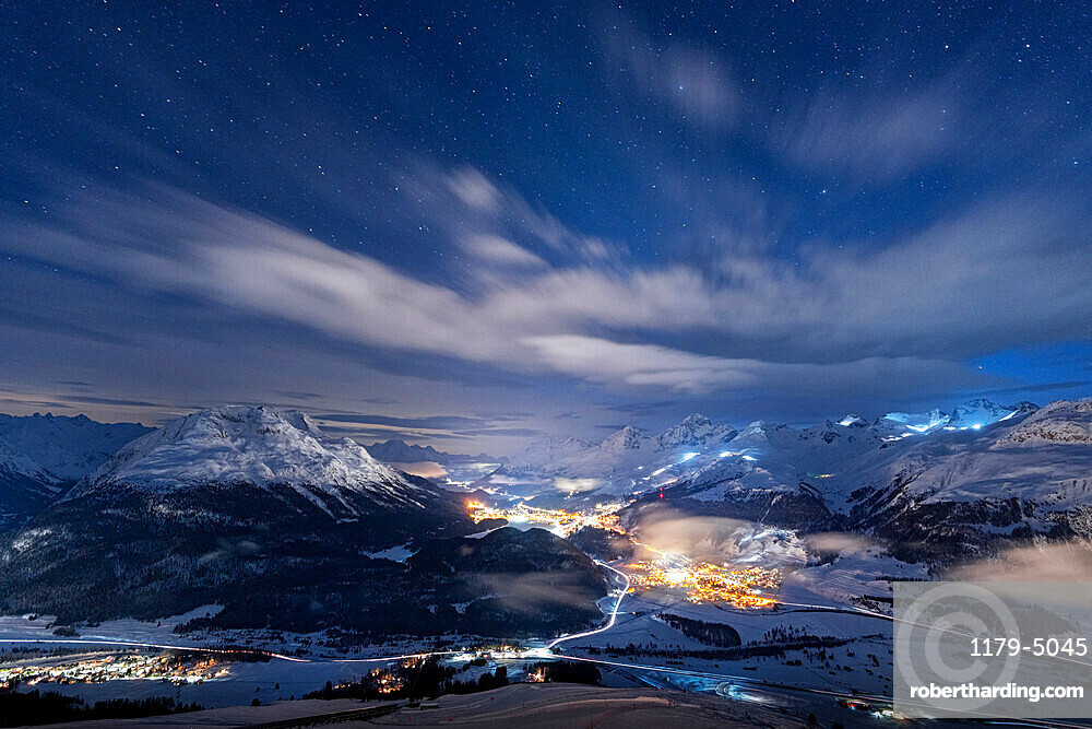 Starry winter sky over St. Moritz village and Upper Engadine covered with snow viewed from Muottas Muragl, Graubunden, Switzerland, Europe