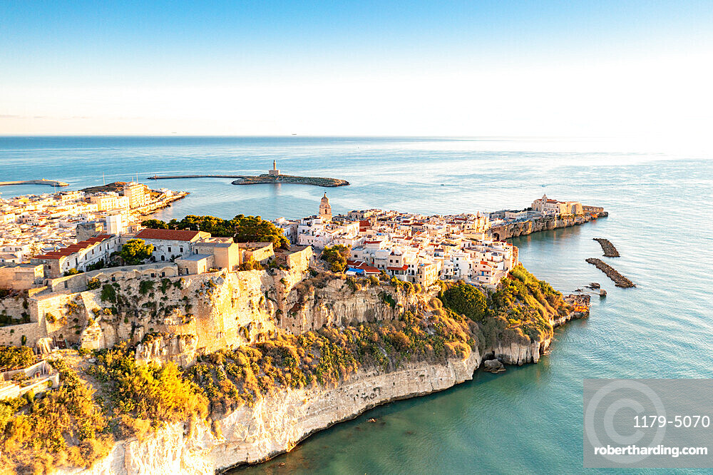 Old town of Vieste perched on cliffs at sunrise, aerial view, Foggia province, Gargano National Park, Apulia, Italy, Europe