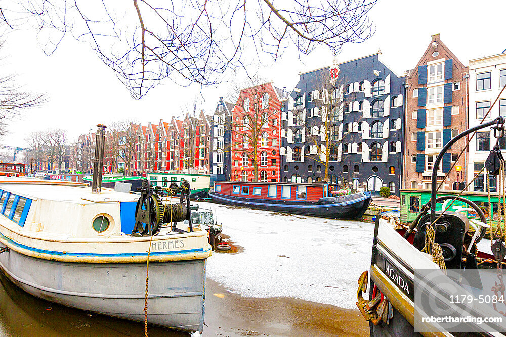 Retro style colorful canal houses on Damrak waterfront, Amsterdam, North Holland, The Netherlands
