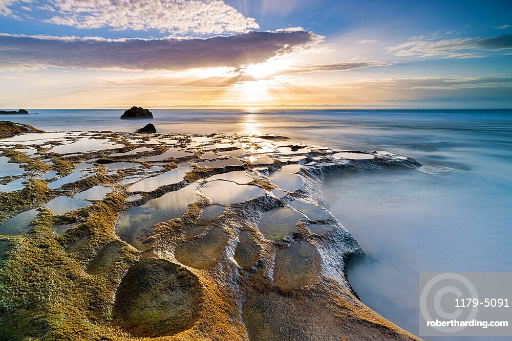 Golden hour over the ocean waves and rocks at El Cotillo beach, Fuerteventura, Canary Islands, Spain