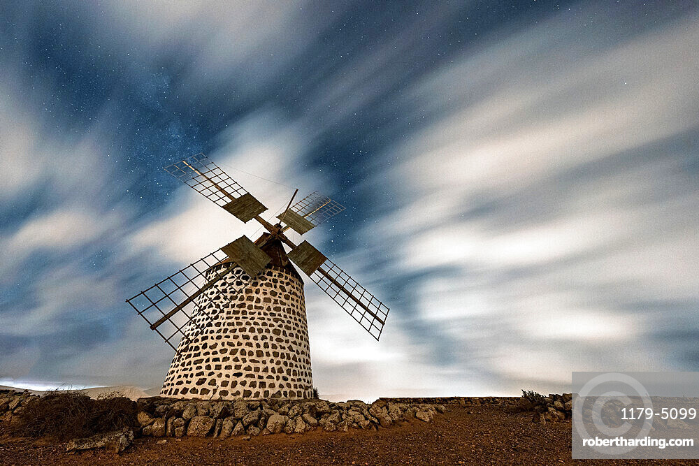 Clouds in the starry sky over the traditional windmill, La Oliva, Fuerteventura, Canary Islands, Spain