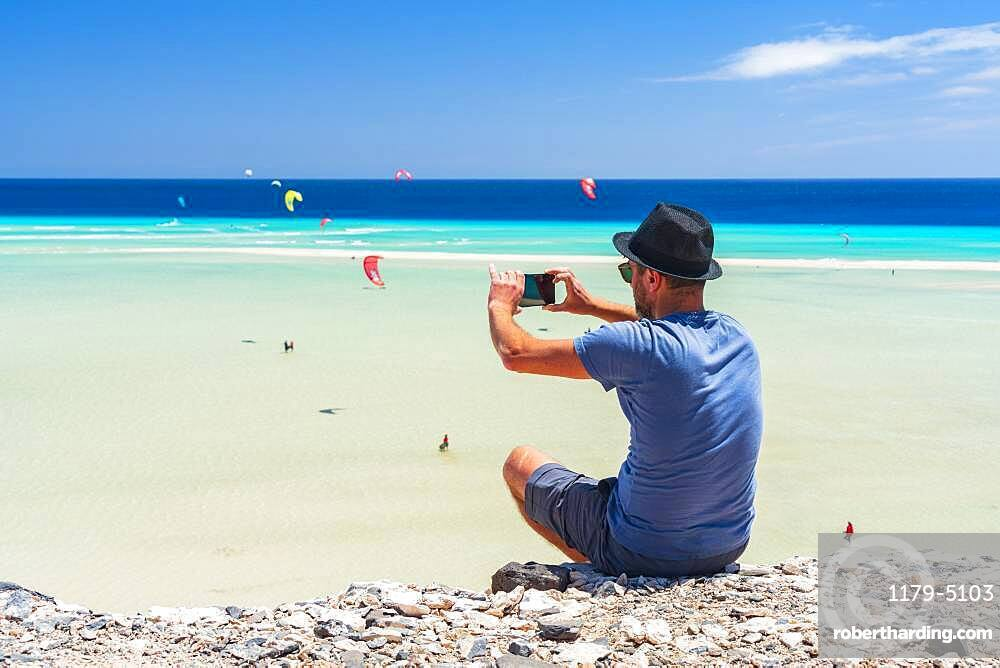 Tourist with straw hat photographing kiteboarders with smartphone at Sotavento beach, Jandia, Fuerteventura, Canary Islands, Spain, Atlantic, Europe