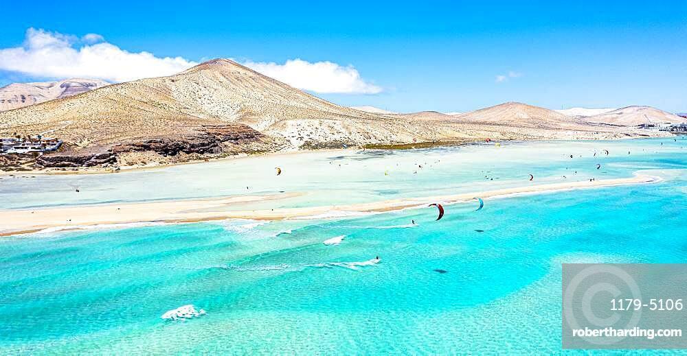 People kiteboarding on waves crashing on white sand of Sotavento beach, Jandia, Fuerteventura, Canary Islands, Spain, Atlantic, Europe