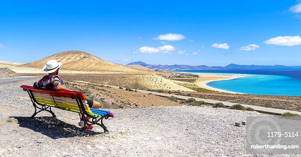 Tourist admiring the crystal ocean from a bench at Mirador Del Salmo viewpoint, Costa Calma, Fuerteventura, Canary Islands, Spain
