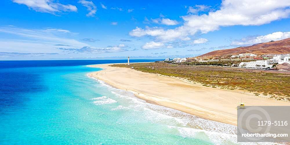 White sand beach washed by the turquoise sea with lighthouse on background, Morro Jable, Fuerteventura, Canary Islands, Spain