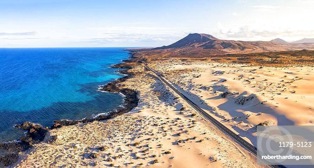 Empty road crossing the sand dunes overlooking the ocean, Corralejo Natural Park, Fuerteventura, Canary Islands, Spain
